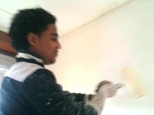 Amin verft voor de eerste keer met een verfroller